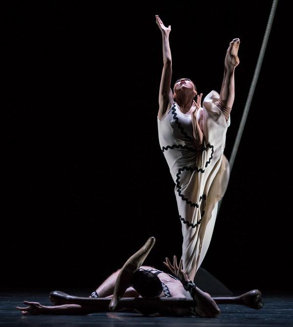 Eine Tänzerin im cremefarbenen Kleid hebt den rechten Arm und das linke Bein gerade nach oben, vor ihr am Boden liegt ein Tänzer mit Hörnern auf dem Kopf