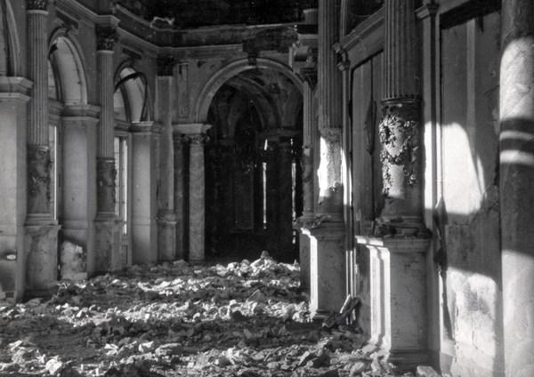 Rundfoyer der zerstörten Semperoper mit Blick auf einen Torbogen, rechts und links sind Säulen zu sehen, der Fußboden ist mit Schutt bedeckt
