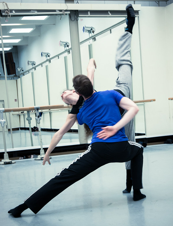 Tänzer und Tänzerin proben im Ballettsaal vor einem großen Spiegel mit Ballettstange