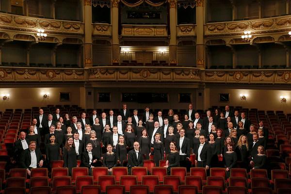 Frauen und Männer in schwarzen Abendkleidern und Anzügen mit weißen Hemden stehen zwischen den samtroten Stuhlreihen des Parketts der Semperoper
