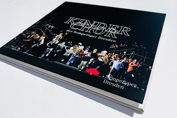 Leicht aufgeklapptes CD-Booklet, oben steht Kinderchor der Semperoper Dresden, darunter ein Szenenfoto aus der Oper »Carmen« mit den Jungen und Mädchen des Kinderchores, die singend auf den Bühnenrand zu marschieren