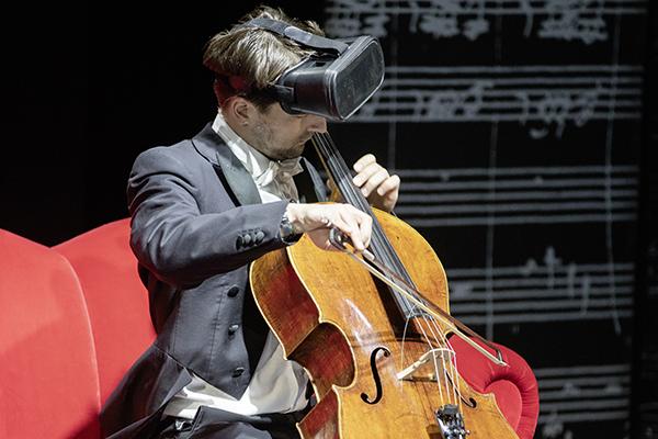 Ein Mann mit einer VR-Brille sitzt auf einem roten Sofa und spielt Cello