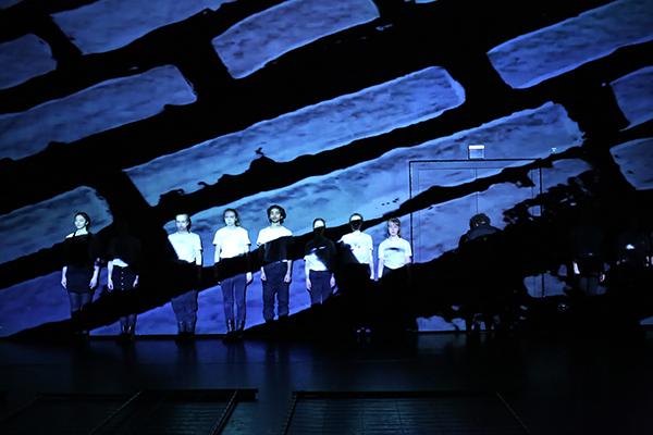 Acht Jugendliche stehen in blauen Hosen und weißen Oberteilen in einer Reihe vor einer dunkelblauen Wand, auf die schwarze Muster projiziert werden, die die Jugendlichen teilweise verdecken