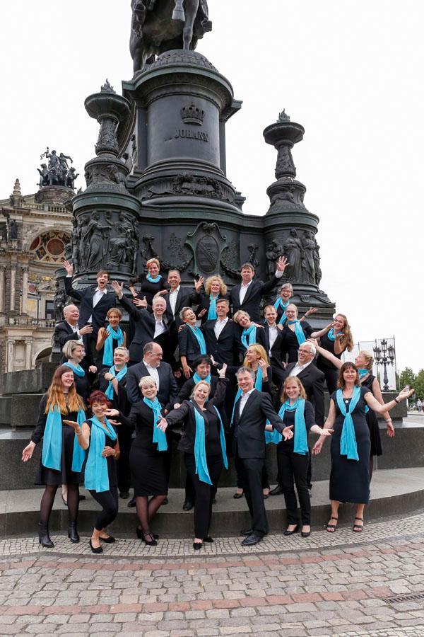 Frauen und Männer in dunklen Kleidern, Kostümen und Anzügen mit hellblauen Schals stehen jubelnd auf den Treppen vor einem Denkmal